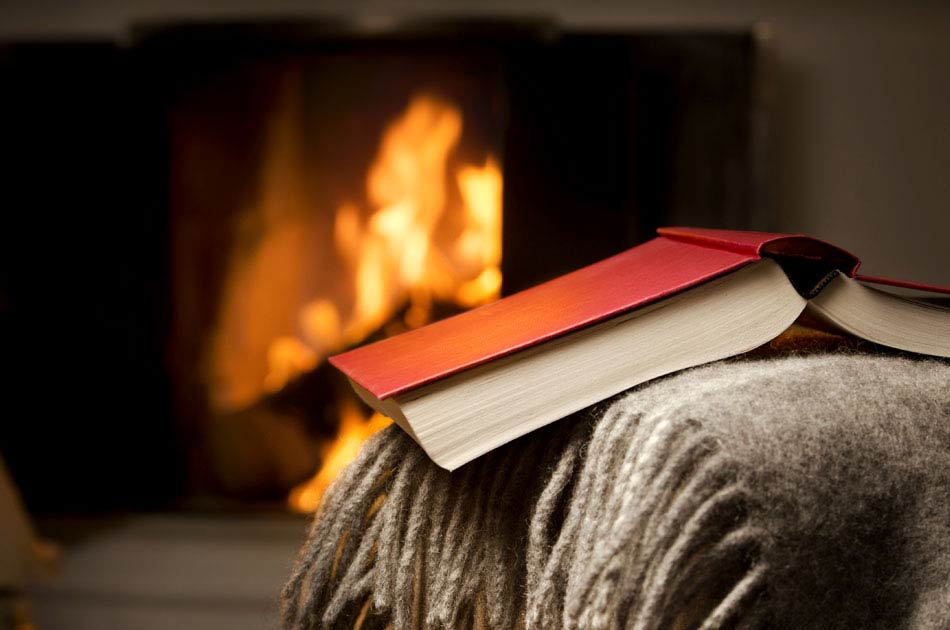 A book sits in front of the fireplace in a study
