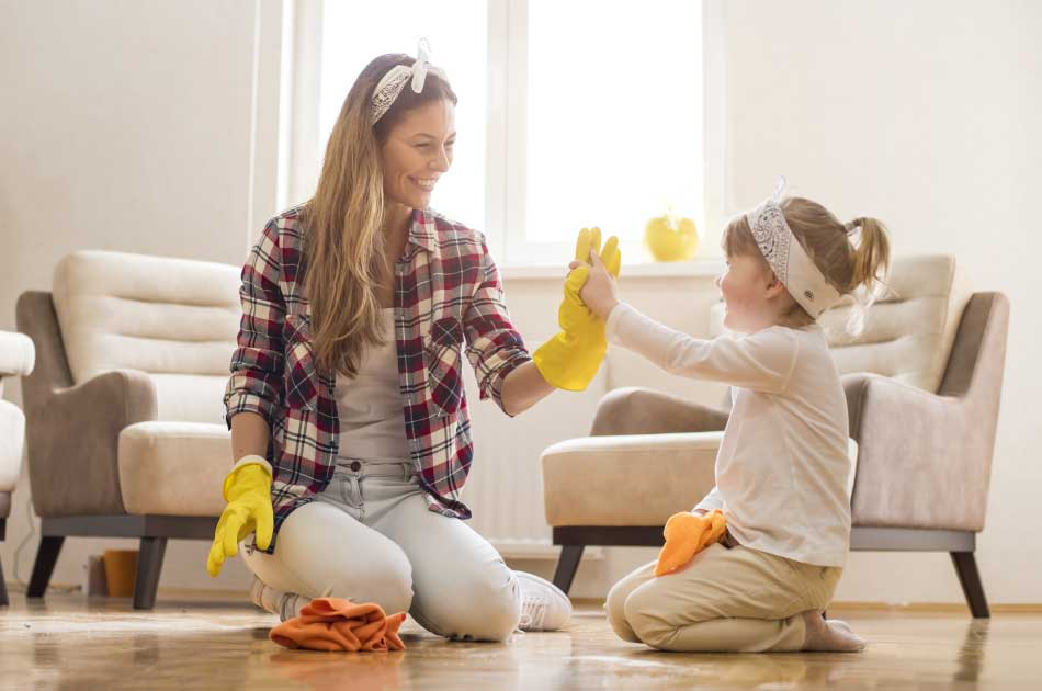 A woman and her young daughter work together spring cleaning their home