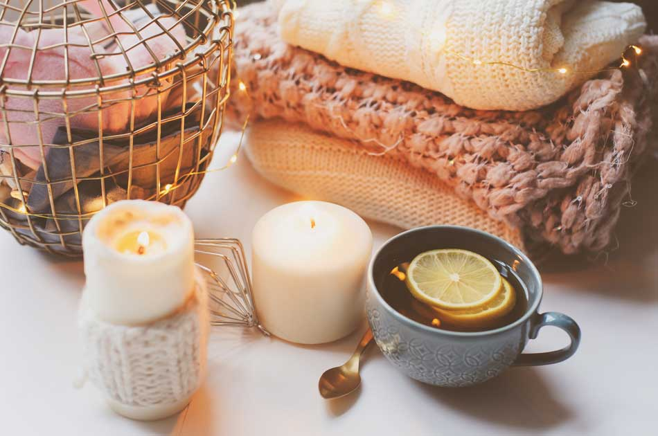 Candles, a warm cup of tea, and knit blankets represent hygge, the Danish art of coziness